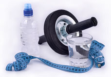 Bottle of water, glass of water, roller wheel for abdominals and. Measuring tape on white Stock Photography