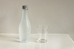Bottle of water and glass on white table Stock Photography