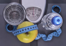 Bottle of water, green apple, glass of water and measuring tape Stock Photos