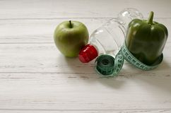 Bottle of water, green apple and pepper, centimeter on white woo Stock Photo