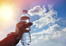A bottle of water in a hand against the sky and sun. Drinking water. Drinking water at dawn. Drinking water sports. Drinking water is healthy Royalty Free Stock Photo