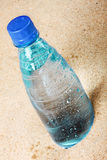 Bottle of water on the hot sand Royalty Free Stock Photo