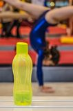 Bottle of water for little gymnast girl. Bottle of water and little gymnast girl practicing in the background Stock Images