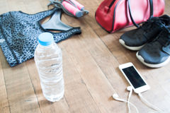 Bottle of water with mobile device and sport equipments on wood Royalty Free Stock Photo