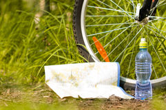 Bottle of water and near bicycle wheel Stock Image