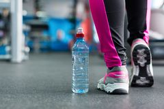A bottle of water near the feet of the girl. Royalty Free Stock Photography