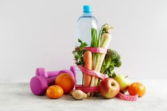 Bottle of water with a pink measuring tape, vegetables and fruit. Concept health, diet and nutrition royalty free stock image