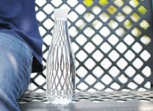 Bottle of water placed on a steel chair beside a man wearing trousers blue jeans in the garden. stock photos