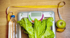 Bottle of water, salad, green apple and weight scale Royalty Free Stock Photo
