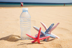 Bottle of water on sandy beach Stock Images