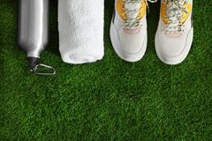 Bottle of water, sneakers, towel and space for text on artificial grass, top view. Fitness equipment stock image