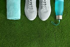 Bottle of water, sneakers, towel and space for text on artificial grass, top view. Fitness equipment stock photos
