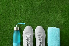 Bottle of water, sneakers, towel and space for text on artificial grass, top view. Fitness equipment royalty free stock photos
