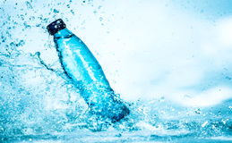 Bottle of water splash. On a blue background royalty free stock image