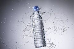 Bottle and water splashes isolated on a white background Royalty Free Stock Photos