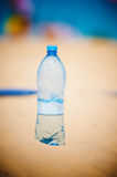 Bottle of water standing in sand at the beach Stock Photo