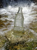 A bottle of water in the stream near the waterfall Royalty Free Stock Photography