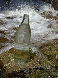 A bottle of water in the stream near the waterfall Royalty Free Stock Images