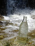 A bottle of water in the stream near the waterfall Royalty Free Stock Photos