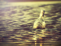 Bottle in water at sunset, retro instagram vintage effect. stock images