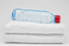Bottle of water and towels. On grey background. Bottle of water and towels. On grey  background Stock Photography