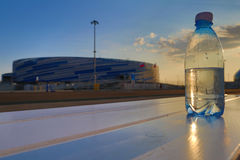 Bottle of water on the white bench. A water bottle stands on the bench during the sunset stock photo