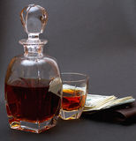 Bottle with whiskey and a glass with whiskey, and a batch of money upon a brown wallet stock photos