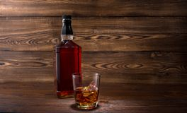 Bottle of whiskey. On a wooden background royalty free stock photography