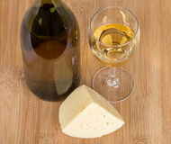 Bottle with white grape wine, piece of cheese and glass Stock Photography