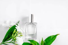A bottle of white perfume and flowers with leaves. Perfume bottle and white flower with green leaf on white background stock image