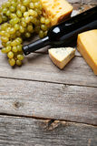 Bottle of white wine, cheeses and grapes on the grey wooden background Stock Image