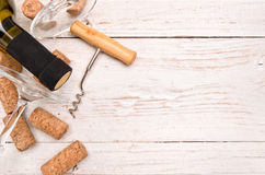 Bottle of white wine, corkscrew and corks on wooden table. Royalty Free Stock Images