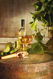 Bottle of white wine with glass on barrel stock image