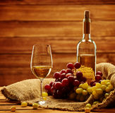 Bottle of white wine, glass and grape on a sack in wooden interi Royalty Free Stock Photo