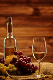 Bottle of white wine, glass and grape on a sack in wooden interi Stock Image