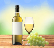Bottle of white wine, glass and green grape on wooden table over Royalty Free Stock Photography
