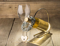 Bottle of white wine and a glass. Shackled love chain with a lock Stock Photography