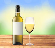 Bottle of white wine and glass on wooden table over nature Royalty Free Stock Photos
