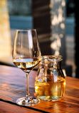 Bottle of white wine and glass on wooden table top. Glass of chilled white wine on table near the beach, in a restaurant tavern Royalty Free Stock Photography