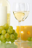 Bottle of white wine, glasses, grape and cheese Royalty Free Stock Photos