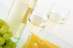 Bottle of white wine, glasses, grape, cheese Stock Image