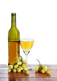 Bottle of white wine and grape bunches Stock Images