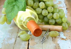 Bottle of white wine, grapes, and a corkscrew Royalty Free Stock Image