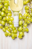 Bottle of white wine and ripe grapes on rustic white wooden background, top view Royalty Free Stock Photo