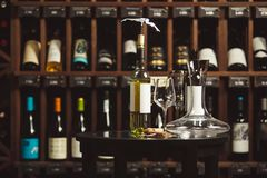 Bottle of white wine on the table next to decanter and glasses over shelf background. Bottle of white wine on the table next to decanter and glasses on shelf Royalty Free Stock Photography