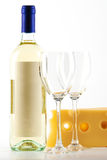 Bottle of white wine, two empty glasses and cheese Stock Image