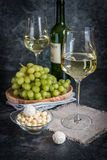Bottle of white wine, two glasses and bunch of grapes Stock Images
