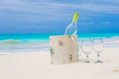 Bottle of white wine and two glasses on the exotic sandy beach Stock Photo