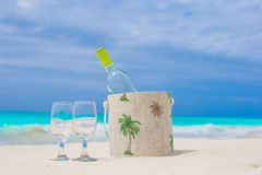 Bottle of white wine and two glasses on the exotic sandy beach. Bottle of wine and two glasses on the white sandy beach stock image
