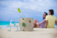 Bottle of white wine and two glasses on the exotic sandy beach. Bottle of wine and two glasses on the white sandy beach stock photography